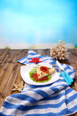 Pancake with red caviar, salmon and mayo, green onion, on plate, on color napkin, on wooden  table, on bright background — Stock Photo