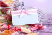 Tasty candies in jar with card on table on bright background — Zdjęcie stockowe