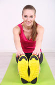 Young beautiful fitness girl exercising on green mat, in gym — Foto de Stock
