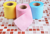 Color toilet paper rolls on bright background — Stock Photo
