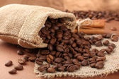 Coffee beans in sack on table close-up — Stock Photo