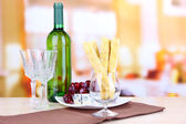 Cheese, grape and bread sticks on plate on wooden table, on bright background — Stock Photo