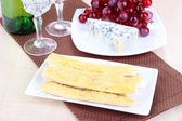 Cheese, grape and bread sticks on plate on wooden table background — Stock Photo