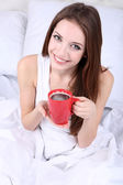 Young beautiful woman with cup of coffee in bed close-up — Stock Photo