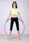 Woman doing exercises with hula hoop in room — Стоковое фото