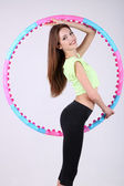 Woman doing exercises with hula hoop in room — Foto Stock