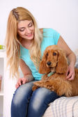 Beautiful young woman with cocker spaniel on couch in room — Stock Photo