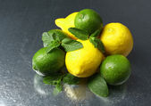 Lemons and limes on dark background — Stock Photo