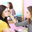 Young woman stylist doing makeup beautiful girl in beauty salon — Stock Photo #42896373