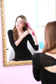 Young beautiful woman making hairstyle near mirror — Stock Photo