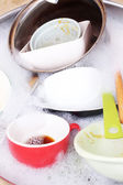 Utensils soaking in kitchen sink — Stock Photo