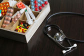 Medical pills,stethoscope,  ampules in wooden box, on color background — Stock Photo