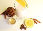Eggnog with spices and orange on yellow background — Stock Photo