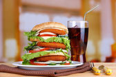 Riesige burger auf farbpalette und kalten getränken, auf hellem hintergrund — Stockfoto