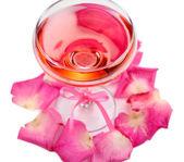 Composizione con rosa sparkle vino in bicchiere e petali di rosa isolati su bianco — Foto Stock