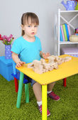 Little girl plays with construction blocks sitting at table in room — Stockfoto