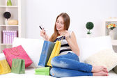 Young woman sitting with  on sofa and holding credit card in her hand, at home — Stock Photo