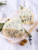 Tasty blue cheese with thyme and olives on wooden table — Stock Photo