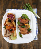 Homemade fried chicken drumsticks with vegetables on plate, on wooden background — Photo