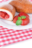 Fresh baked pasties with strawberries on plate on table close-up — Stock Photo