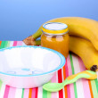 Jar of baby puree with plate and spoon on napkin on blue background — Stock Photo #42965175