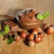 Sweet chocolate hazelnut spread with whole nuts and mint on wooden background — Stock Photo