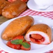 Fresh baked pasties with strawberries on plate on table close-up — Stock Photo #42967511