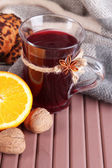 Mulled wine with orange and nuts on table on fabric background — Stock Photo
