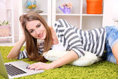 Young woman resting with laptop on floor near sofa, at home — 图库照片