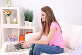 Young woman resting with laptop on sofa at home — 图库照片