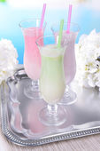 Milk shakes on table on light blue background — Stock Photo