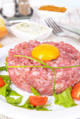 Delicious steak tartare with yolk on plate on table close-up — Stock Photo