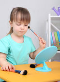 Little girl doing makeup sitting at table in room — Stock Photo