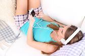 Young girl listen to music on home interior background — Stock Photo