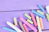 Chalks in variety of colors, on wooden background — Stock Photo