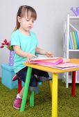 Little girl reads book sitting at table in room — Stock Photo