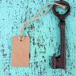Key with empty tag, on color wooden background — Stock Photo