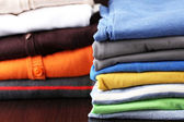 Stack of colorful clothes, on dark background — Stock Photo