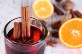 Mulled wine with oranges and spices on wooden background — Stock Photo