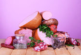 Lot of different sausages on wooden table on purple background — Stock Photo