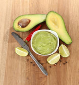 Fresh guacamole in bowl on wooden table — Stock Photo