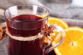 Mulled wine with oranges fabric background — Stock Photo