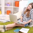 Young woman resting with laptop on floor near sofa, at home — Stock Photo #42996177