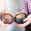 Two ceramic pots with golden coins in male and female hands, on light background — Stock Photo