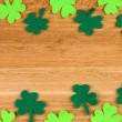 Clover leaves on wooden background — Stock Photo