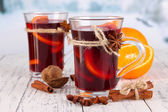 Mulled wine with oranges and spices on table on bright background — Stock Photo