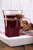 Mulled wine with cookies on table on wooden background — Stock Photo
