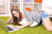 Young woman resting with laptop on floor near sofa, at home — Stockfoto
