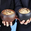 Two ceramic pots with golden coins in male and female hands, on color background — Stock Photo #43001861