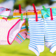 Baby clothes hanging on clothesline, on bright background — Stockfoto